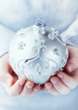 A child holding silver christmas ball Stock Photo