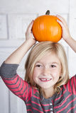 Child holding small pumpkin on her head Stock Photography