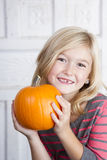 Child holding small pumpkin up by her face Royalty Free Stock Photos
