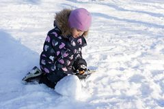Child holding snow and playing on winter snowy day. On the nature Stock Images