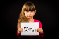 Child holding Sorry sign. Studio shot of child holding a Sorry sign made of white paper with handwriting Stock Photo