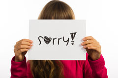 Child holding Sorry sign. Studio shot of child holding a Sorry sign made of white paper with handwriting Royalty Free Stock Photo