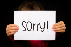 Child holding Sorry sign. Studio shot of child holding a Sorry sign made of white paper with handwriting Stock Images