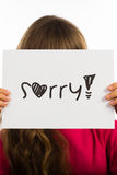 Child holding Sorry sign. Studio shot of child holding a Sorry sign made of white paper with handwriting Stock Image