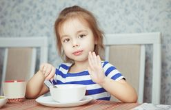 Child holding spoon in her hand eating dish stock image