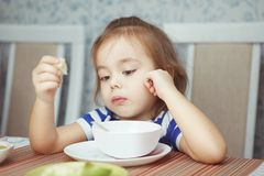 Beautiful Child eating dish at table stock photography