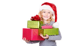 Child holding a stack of Christmas presents. Young child holding large stack of Christmas presents wearing a Santa hat isolated on white stock images