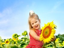 Child holding sunflower outdoor. Royalty Free Stock Images