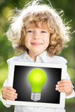 Child holding tablet PC with lightbulb. Child holding tablet PC with green light bulb on screen against blurred spring background. Creativity technology concept Royalty Free Stock Photography