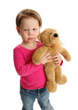 Child holding a teddy bear with mad expression. Little toddler girl holding on to a teddy bear. She has a mad, angry, sad, or skeptical expression on her face Stock Images