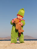 Child holding teddy bear. Child playing with teddy bear at the beach Royalty Free Stock Image