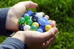 Child holding two hands full of marbles Stock Photo
