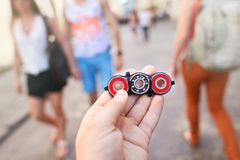 . Child holding unusual metal spinner at blurry people in the street background. Closeup of hand of kid playing modern popular hand toy spinner made by himself royalty free stock photos