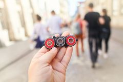 . Child holding unusual metal spinner at blurry people in the street background. stock photos