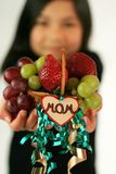 Child holding up fruit basket Royalty Free Stock Images