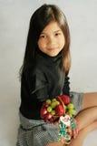 Child holding up fruit basket Stock Image