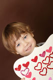 Child holding Valentine's Day Craft with Hearts Royalty Free Stock Images