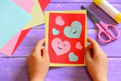 Child is holding a Valentines greeting card in his hands. Child is showing a Valentines greeting card. Simple paper crafts Stock Image