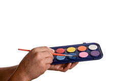 Child holding a watercolour paint set. And a brush in his hand Royalty Free Stock Photos