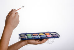 Child holding a watercolour paint set. And a brush in his hand Royalty Free Stock Photo