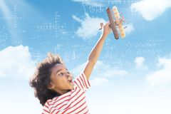 Composite image of child holding wooden airplane. Child holding wooden airplane against blue sky Royalty Free Stock Photos