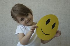 A kid holding a yellow circle with smile face emoticon instead of head. Royalty Free Stock Photography