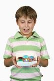 Child holding yummy cupcakes. Child holding some delicious cupcakes in his hands and looking down at them royalty free stock images