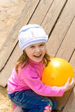 Child holds a ball. The child on a playground holds a yellow ball Royalty Free Stock Photography
