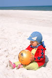 Child holds ball. Small girl holds orange ball in hands royalty free stock photography