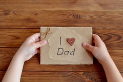 Child holds a birthday card for dad. Child holds a greeting card in hands. I love dad. Hand card out of cardboard, paper, wood buttons, cord. Simple quick gift Stock Images