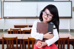 Child holds a book and apple in classroom Royalty Free Stock Image