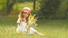 Child holds a bouquet of wildflowers in her hands, she smells them and smiles stock video footage