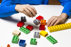 Child holds building blocks in his hands and play in kindergarten or at home Stock Images