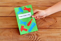 Child holds a card in hand. Greeting card father's day. Happy father's day. Paper craft idea for kids. Greeting card Stock Photo