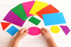 Child holds cardboard pink oval in the hands. Child learns colors and geometric shapes. Developing skills in kids. Reach concept. Royalty Free Stock Image
