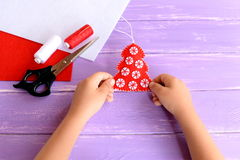 Child holds Christmas tree ornament in his hands. Red felt tree with white balls, scissors, thread, needle, felt sheets Stock Image