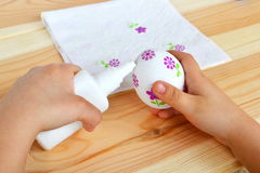 Child holds a decoupage Easter egg and glue in hands. Child glues the flower fragments of napkin to the egg. Easter decoupage. How to make decorated egg with Stock Photo