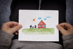 Child holds a drawn house with family Royalty Free Stock Photos