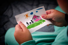 Child holds a drawn house with family. Close up. Vignette Stock Photo