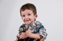 Child holds drill in hand Royalty Free Stock Photo