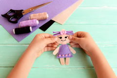 Child holds a felt doll in his hands and shows it. Scissors, thread, felt sheets on a table. Cute stuffed toy is made manually Royalty Free Stock Photos
