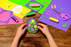 Child holds a felt Easter egg decor in his hands. Child made simple Easter crafts. Sewing tools and materials on a wooden table Stock Photo