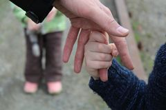 The child holds the finger of the father`s hand against the background of another child`s brother or sister stock photos