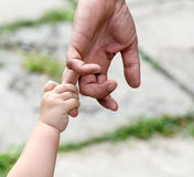 Child holds the finger of a hand of the father Stock Photos