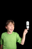 Child holds fluorescent globe. A boy holds an energy efficient compact fluorescent light bulb with space for your text or message. vertical stock photos