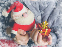 Child holds gift box and toy Santa Claus, Christmas and New Year. Child holds in his hands gift box and toy Santa Claus, Christmas and New Year background Stock Photos