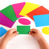 Child holds green cardboard rectangle in hands and looking for corresponding color card.Kid learns colors and form with paper card. Concept development in royalty free stock photo