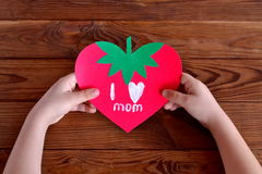 Child holds greeting card in his hands. Paper card strawberry. Greeting card mother's day Stock Images