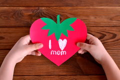 Child holds greeting card in his hands. Paper card strawberry Royalty Free Stock Photo