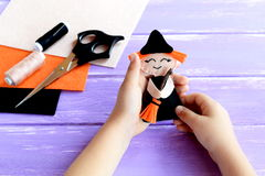 Child holds a Halloween witch doll in his hands and shows it. Scissors, thread, needle, felt on a wooden table. Creative witch DIY Royalty Free Stock Photo